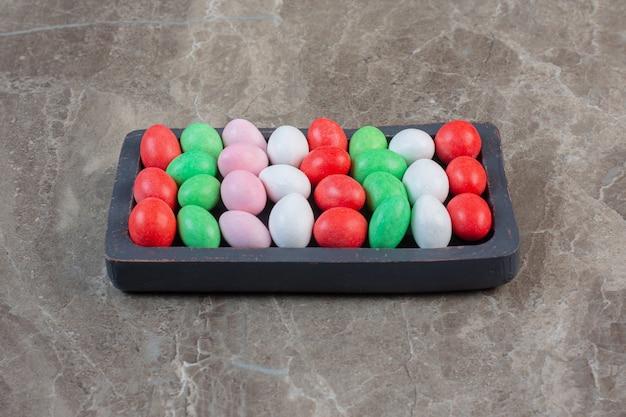 Jasne kolorowe żelki. oddziel kolory na drewnianym talerzu.