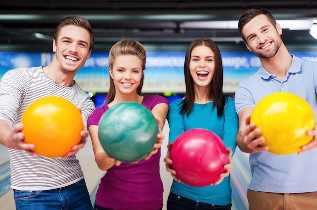 Jasne kolory najlepszej gry. wesoli przyjaciele patrzący w kamerę i wyciągający piłki, stojąc przed kręgielniami