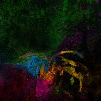 Jasne kolory rangoli rozłożone na czarnej powierzchni