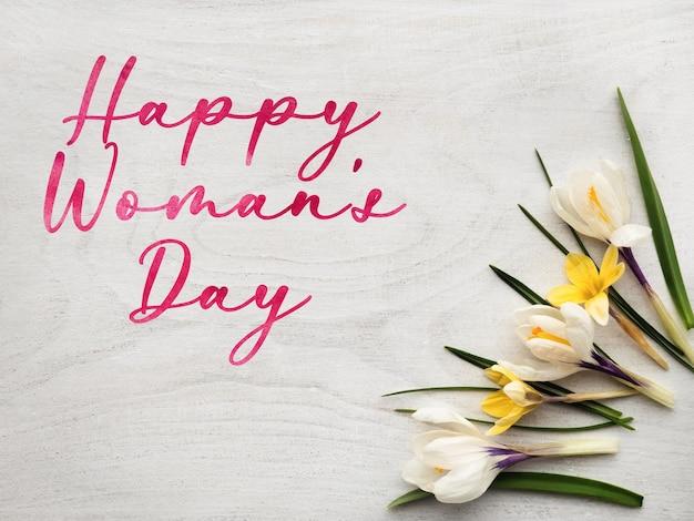 Jasne kwiaty i napis happy women's day. zbliżenie, brak ludzi, tekstura. gratulacje dla rodziny, krewnych, przyjaciół i współpracowników