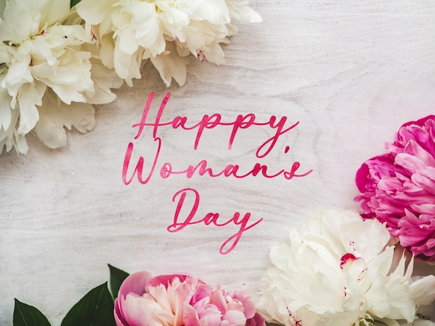 Jasne kwiaty i napis happy women's day.