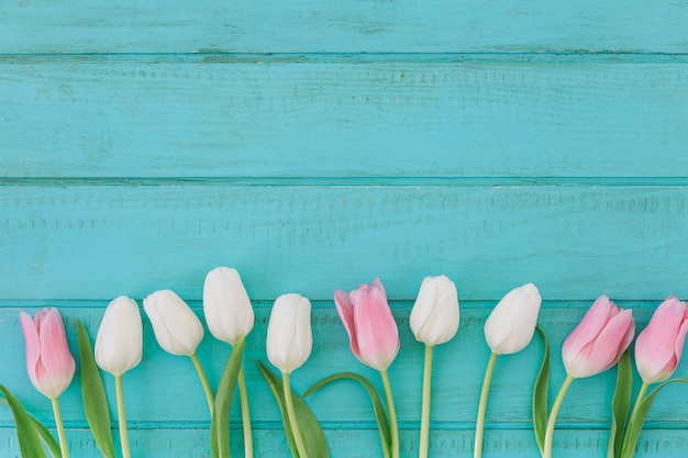 Jasne kwiaty tulipanów na drewnianym stole