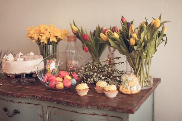 Jasne makaroniki i babeczki na drewnianym stole. w pomieszczeniach naturalne światło przy niewielkiej głębi ostrości