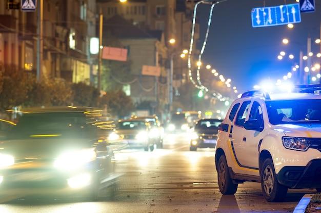 Jasne migające niebieskie światła policyjnego samochodu patrolowego zaparkowanego na ulicy miasta z nocnym ruchem.