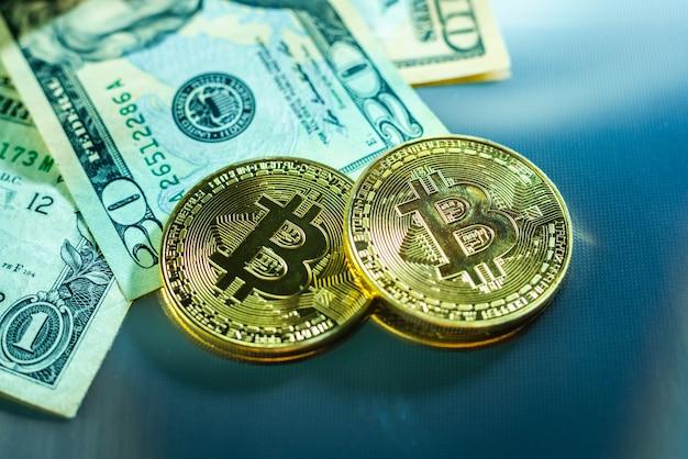 Jasne monety bitcoin obok banknotów dolarowych.