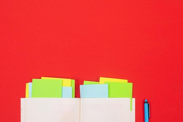 Jasne naklejki, notatnik i długopis na białym tle na czerwonym tle