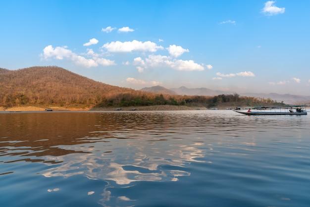 Jasne niebo, góry i odbicia na powierzchni jeziora.