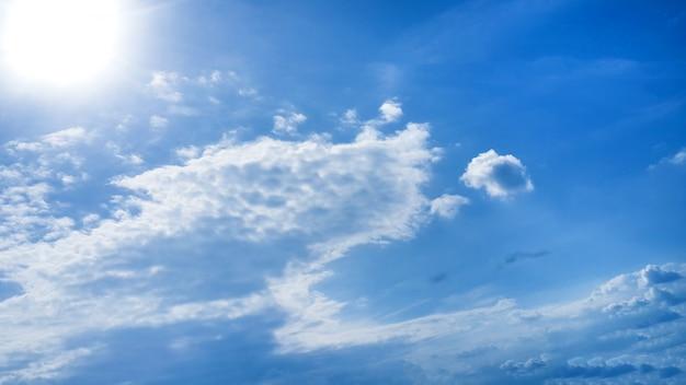 Jasne niebo z chmurami i słońce w tle