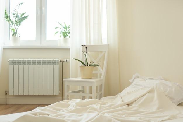 Jasne pastelowe wnętrze sypialni, łóżko, białe krzesło, okno, lekkie zasłony.