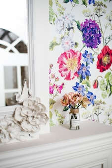 Jasne pionowe wnętrze z kolorową tapetą. bukiet kwiatów stoi w wazonie na białym kominku. piękne wnętrze drogiego pokoju