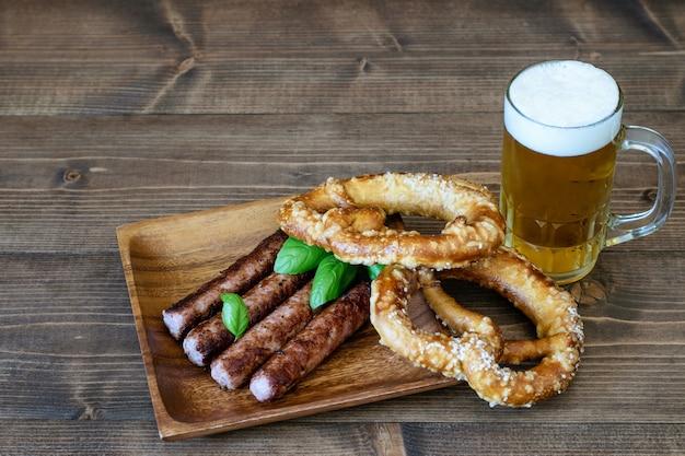 Jasne piwo podawane ze smażonymi kiełbaskami i preclami na drewnianym stole