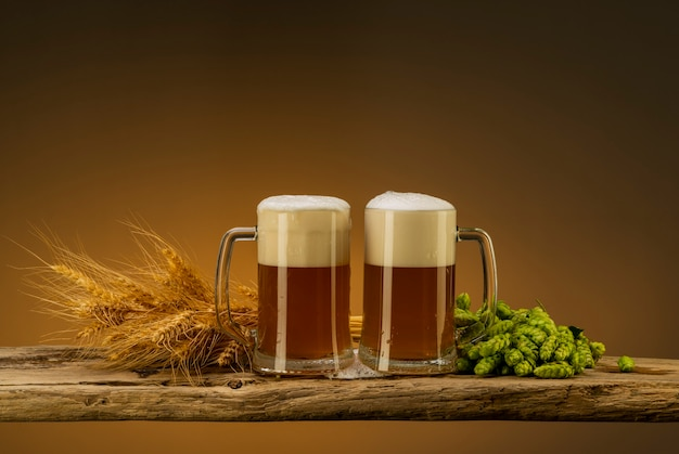 Jasne piwo z pianką w kubkach, chmielu i pszenicy przy szklankach na stole
