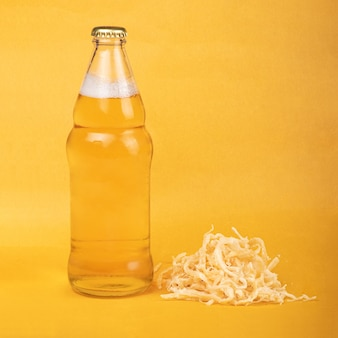 Jasne piwo z suszonymi owocami morza kalmarów z alkoholem na żółtym tle