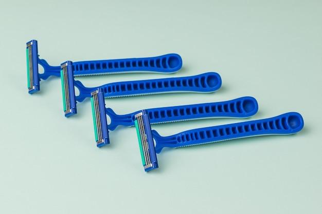 Jasne plastikowe jednorazowe maszynki do golenia dla mężczyzn na niebieskiej powierzchni. narzędzia do pielęgnacji twarzy. zestaw do pielęgnacji męskiej twarzy.