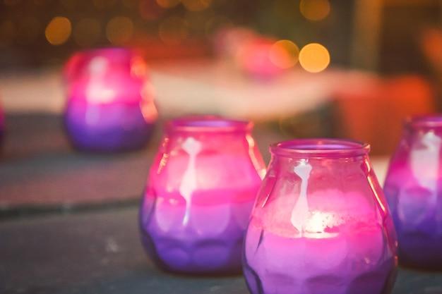 Jasne płonące fioletowe i różowe świece na stole