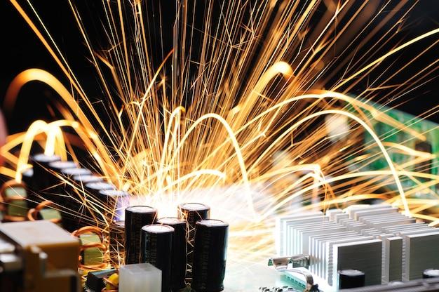 Jasne płonące iskry lecą z chipa złożonego sprzętu wojskowego