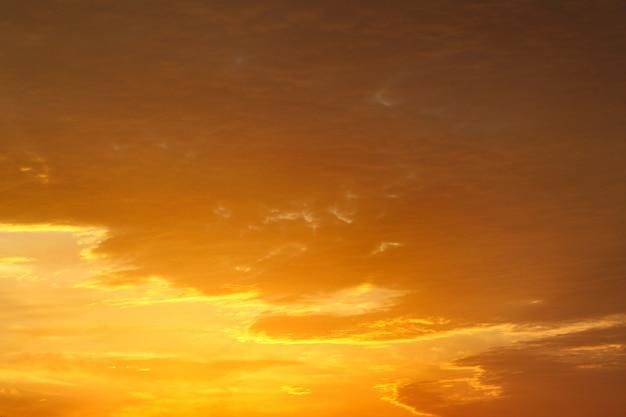 Jasne pomarańczowe i żółte kolory zachodzącego nieba z grubymi chmurami.