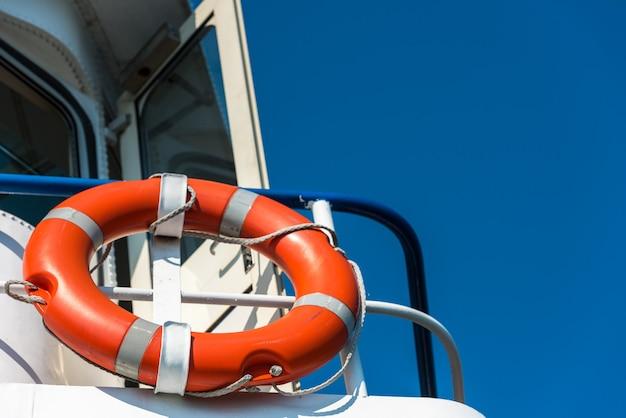 Jasne pomarańczowe koło ratunkowe po białej stronie jachtu.