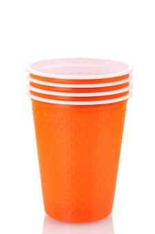 Jasne pomarańczowe kubki plastikowe na białym tle
