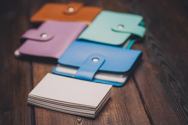 Jasne posiadacze wizytówek na tekstury tła drewniane paczce białego papieru