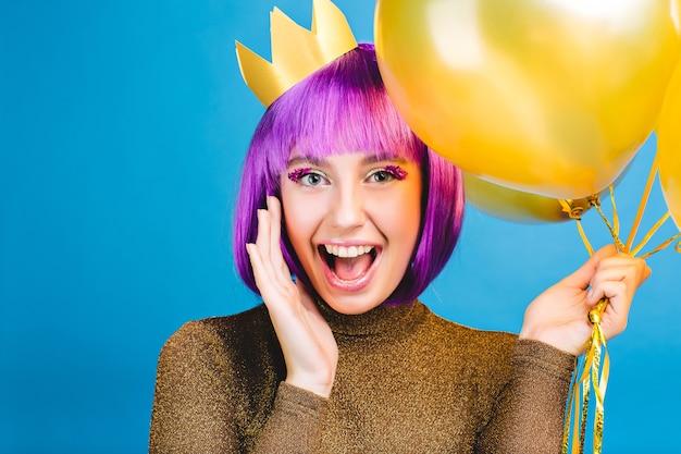 Jasne pozytywne emocje podczas świętowania nowego roku, przyjęcie urodzinowe zabawnej, radosnej młodej kobiety z obciętymi fioletowymi włosami. złote balony, korona na głowie, luksusowa sukienka, szczęście.