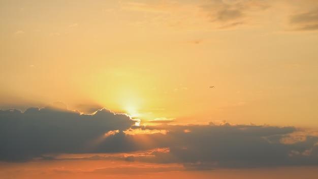 Jasne promienie słoneczne na pomarańczowym niebie słońca z chmurami cumulus