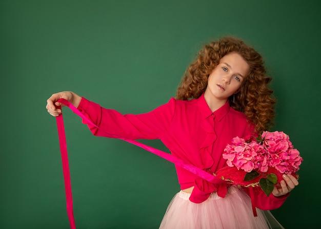 Jasne redhair nastolatka dziewczyna w różowej sukience na zielonym tle trzyma bukiet kwiatów ze wstążką w ręce.