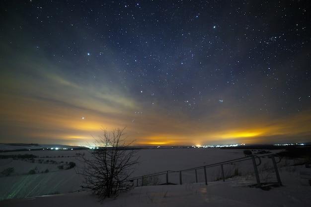 Jasne rozgwieżdżone nocne niebo nad śnieżnym krajobrazem w dolinie wzgórz