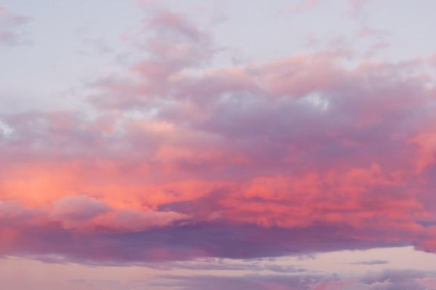 Jasne różowe chmury na niebieskim niebie o zachodzie słońca