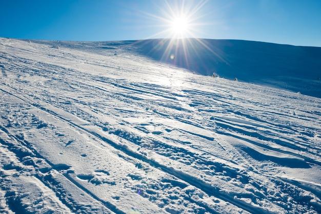 Jasne słońce w zimowych górach pokrytych śniegiem.