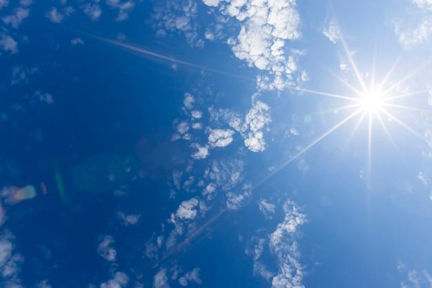 Jasne słońce z odchodzącymi od niego białymi promieniami. na niebieskim niebie są chmury oświetlone światłem słonecznym.