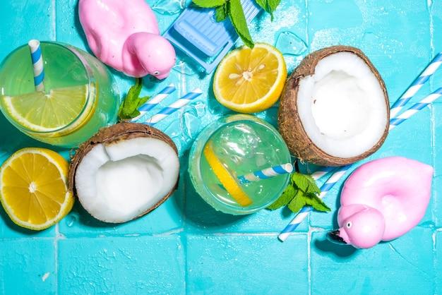Jasne słoneczne letnie wakacje. napój lemoniadowy na mokrym niebieskim tle płytek basenowych, z akcesoriami do wakacji na plaży, kołami ratunkowymi flamingów, cytrynami, kokosami, miętą, tropikalnymi liśćmi, kopią miejsca z widokiem z góry