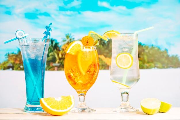 Jasne smaczne napoje w zdobionych szklankach i plasterkach cytrusów