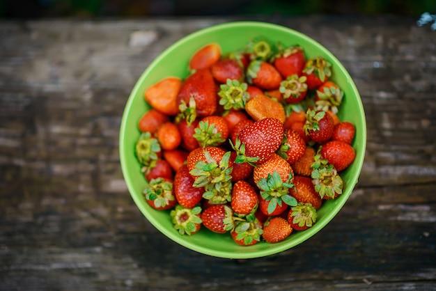 Jasne soczyste pachnące dojrzałe truskawki w zielonym talerzu.