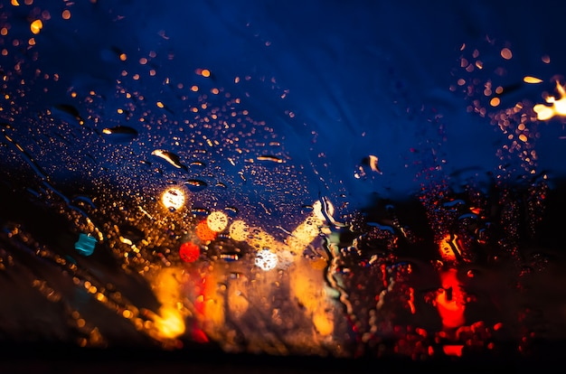 Jasne światła nocnego miasta przez szybę w kroplach deszczu.