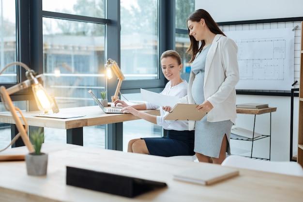 Jasne światło. zbliżenie na miejsce pracy z lampą i tabletem, podczas gdy pozytywni koledzy mają ważną dyskusję