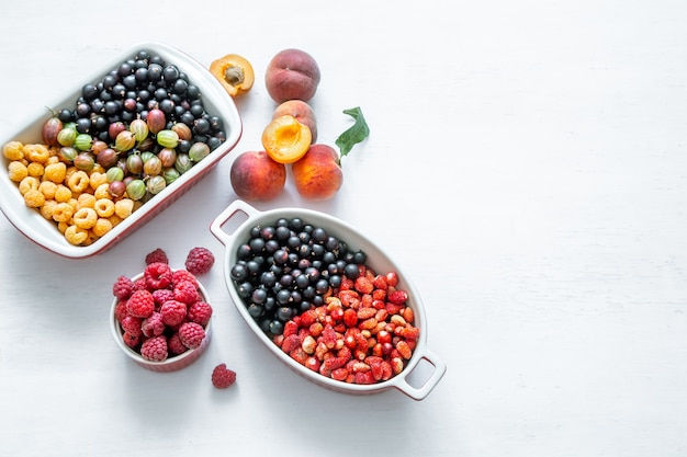 Jasne, świeże dzikie jagody i brzoskwinie na białym tle widok z góry. pojęcie zdrowego odżywiania.