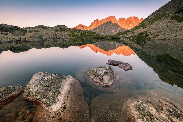 Jasne szczyty górskie odbicie w jeziorze rano