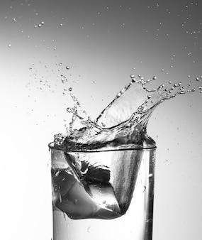 Jasne szkło wody splash zatrzymać działania na białym tle gradientu
