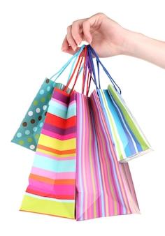 Jasne torby na prezent w ręku na białym tle