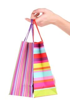 Jasne torby na prezenty w ręku na białym tle