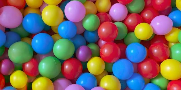 Jasne wielokolorowe kulki do suchego basenu do gier dla dzieci. zabawki, rozwój dla dzieci. jasne wielokolorowe tło.