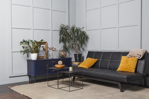 Jasne wnętrze apartamentu z czarną skórzaną sofą, zdobionym kinkietem i stołem.