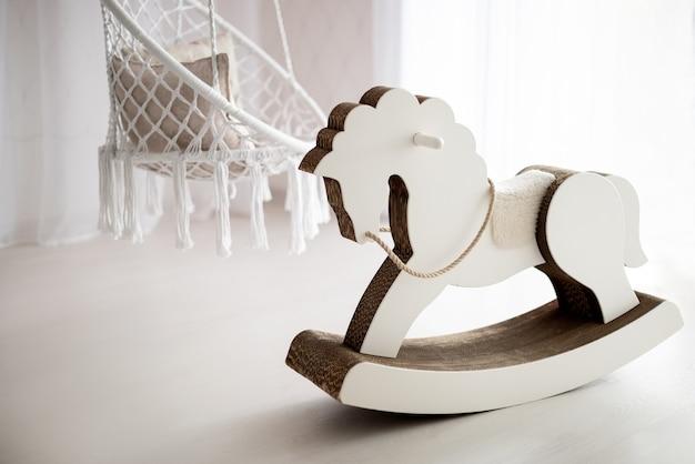 Jasne wnętrze pokoju dziecięcego z wiklinowymi huśtawkami i białym konikiem na biegunach