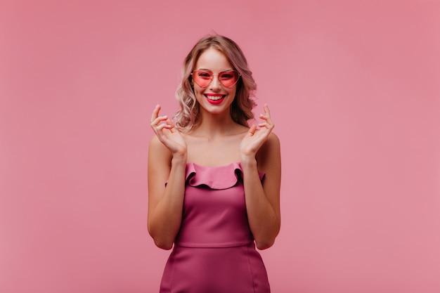 Jasne zdjęcie studyjne uroczej, przyjaznej modelki europejskiej z czarującym uśmiechem i dołeczkami