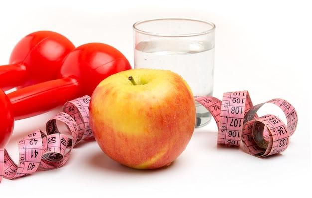 Jasne żółte jabłko ze szklanką wody i czerwone hantle, miara na białym tle