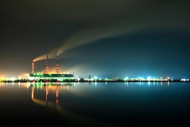 Jasno oświetlone wysokie rury elektrowni węglowej z czarnym dymem unoszącym się w górę zanieczyszczającą atmosferę nocą z jej odbiciami w wodzie jeziora.