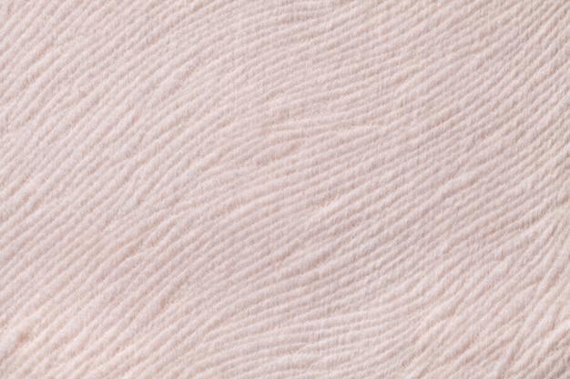Jasnobeżowe tło z miękkiego materiału tekstylnego. materiał o naturalnej fakturze.