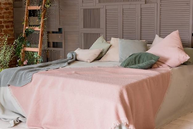 Jasnobeżowy różowy koc na łóżku z zielonymi miętowymi poduszkami. stylowe przytulne skandynawskie wnętrze sypialni: łóżko, drewniana drabina, drewniana ściana. wnętrze mieszkania na poddaszu. minimalistyczne wnętrze