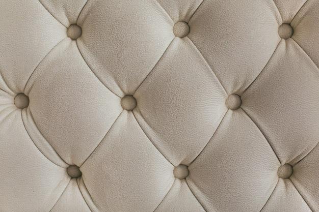 Jasnobeżowy welurowy materiał w romby z guzikami. koncepcja tła. pokrowiec na sofę.